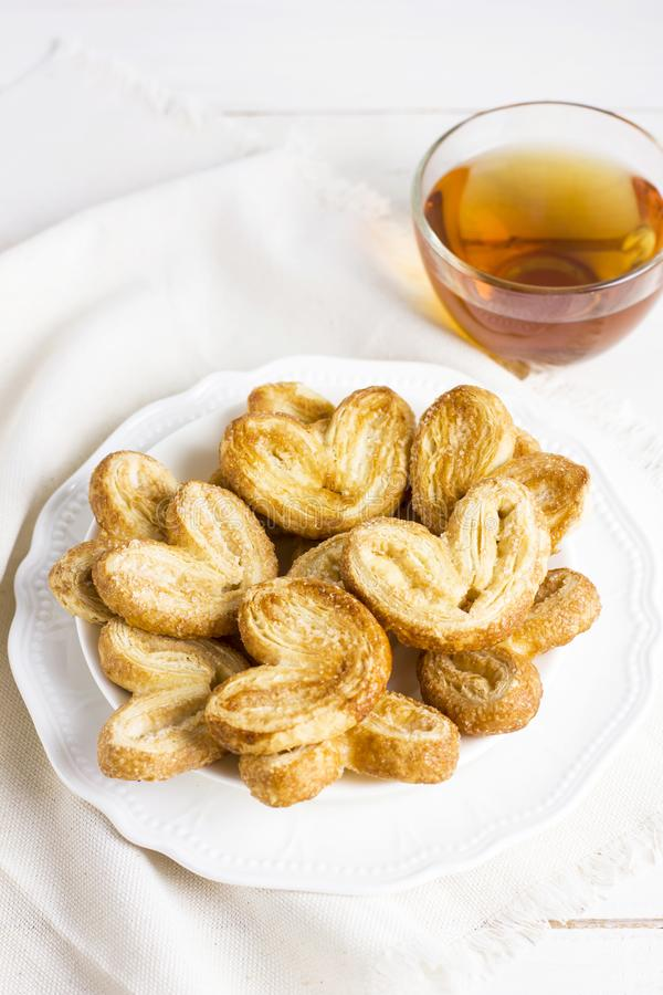 Сердца печенья слойки на белой плите с чашкой чаю стоковая фотография rf