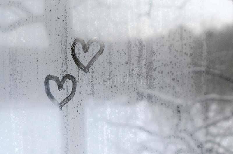 2 сердца покрашенного на misted стекле в зиме стоковое изображение