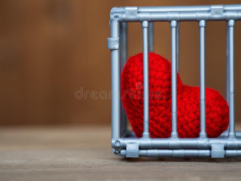 Сердце в клетке положенной на деревянный стол, оно показывает закрытие свободы и влюбленности Влюбленность разочарованна и не удо стоковое изображение rf