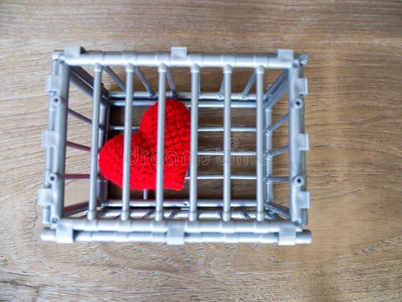 Сердце в клетке положенной на деревянный стол, оно показывает закрытие свободы и влюбленности Влюбленность разочарованна и не удо стоковое фото