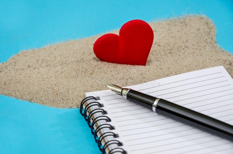 Сердце в песке, ноутбуке и ручке на синем фоне Закрыть стоковая фотография