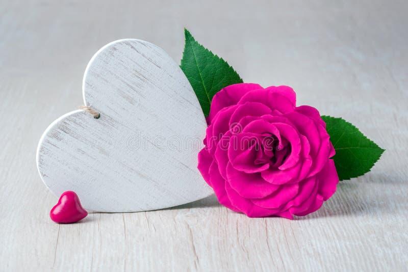 Сердце и розовые цветки на деревенской таблице - концепции валентинки стоковая фотография