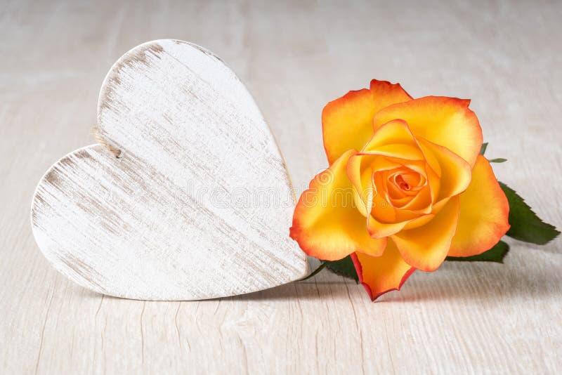 Сердце и розовые цветки на деревенской таблице - полюбите концепцию стоковое фото rf