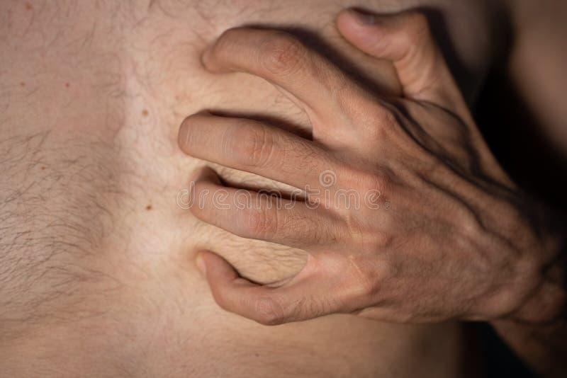 Сердце кавказской руки человека левой хватая сильно стоковые изображения