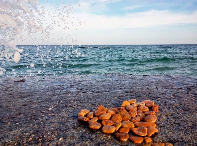 Сердце камней клало вне на пристань моря стоковое фото rf