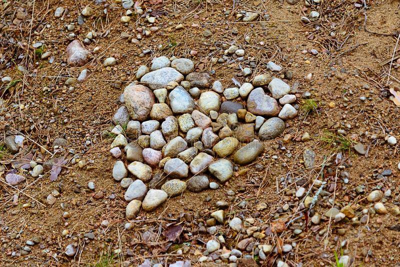 Сердце камней положенных вне на том основании стоковые изображения