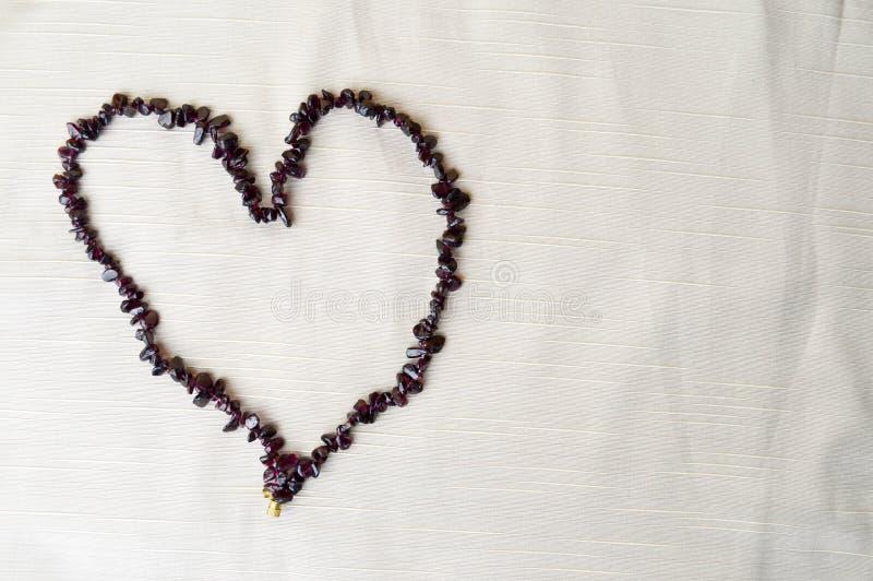 Сердце клало из женских красивых шариков, ожерелиь коричневых темных камней, янтарных против предпосылки бежевой ткани стоковое фото