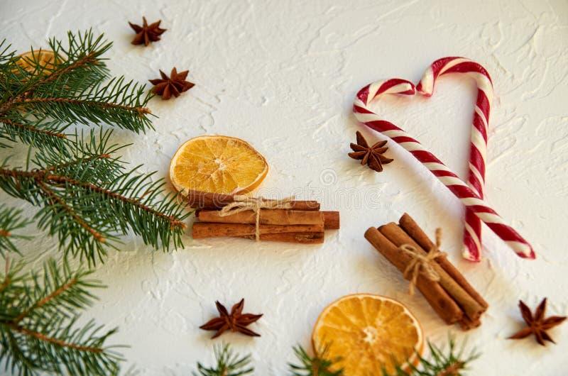 Сердце красных конусов конфеты на белой таблице с звездами анисовки специй, ручками циннамона, высушило апельсины и ветви ели стоковое изображение