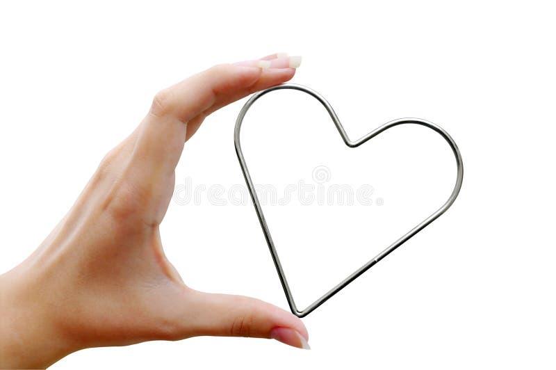 Сердце металла в женской руке стоковое изображение rf
