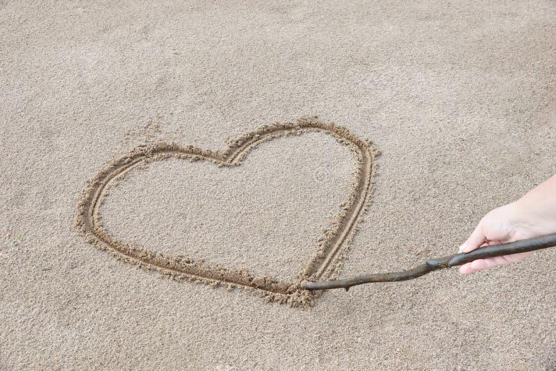 сердце нарисовано на песке на пляже с ручкой вы можете стоковые фотографии rf