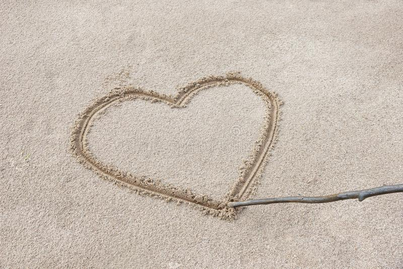 сердце нарисовано на песке на пляже с ручкой стоковые фото