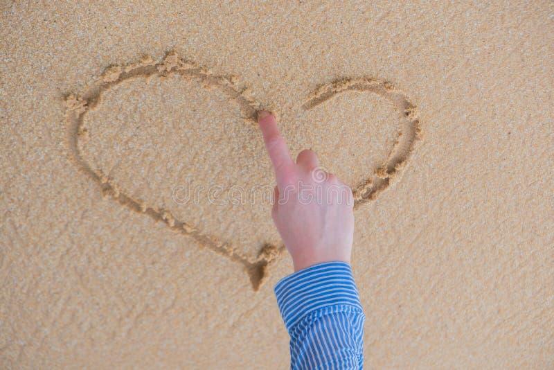 Сердце нарисовано с пальцем на песке около океана стоковое изображение
