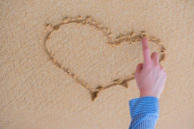 Сердце нарисовано с пальцем на песке около океана стоковые фотографии rf