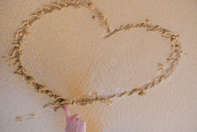 Сердце нарисовано с пальцем на песке около океана стоковые изображения