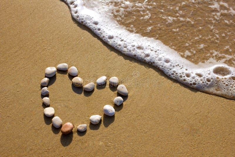 Сердце на пляже стоковые изображения