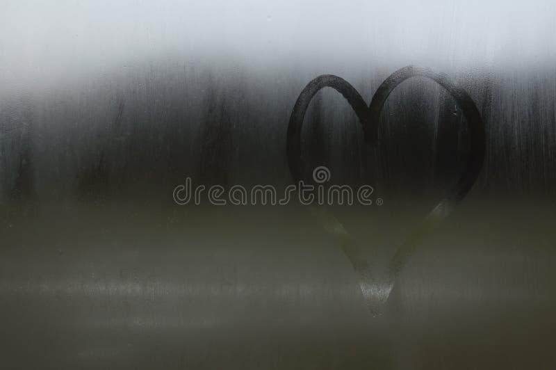 Сердце пальца нарисовано на окне вспотело Сердце покрашено на стекле или на зеркале стоковая фотография rf