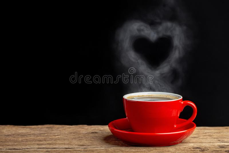 Сердце пара завиша над красной чашкой кофе кофе на деревянном столе с черной предпосылкой стоковые изображения rf