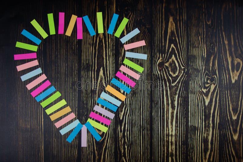 Сердце пестротканых стикеров На темно-синей предпосылке деревянного стола Валентайн дня s Валентайн формы влюбленности сердца кар стоковое фото rf