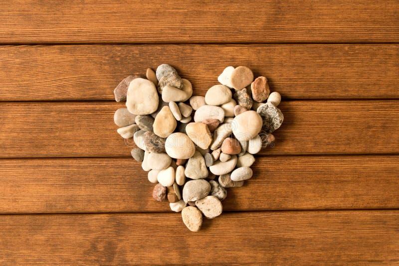Сердце положенное из камней на деревянный стол Взгляд сверху Концепция стоковые изображения