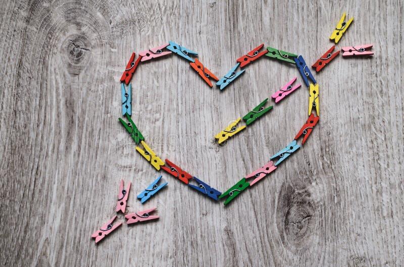 Сердце прокалыванное стрелкой сделанной деревянных зажимок для белья стоковые фотографии rf