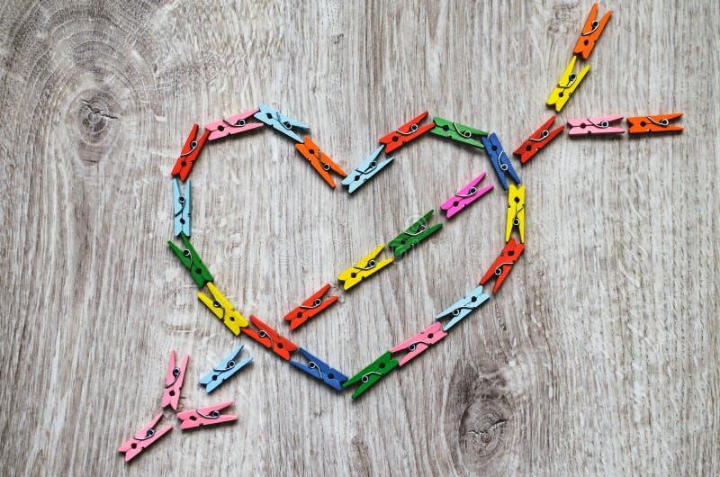 Сердце прокалыванное стрелкой сделанной деревянных зажимок для белья стоковые изображения