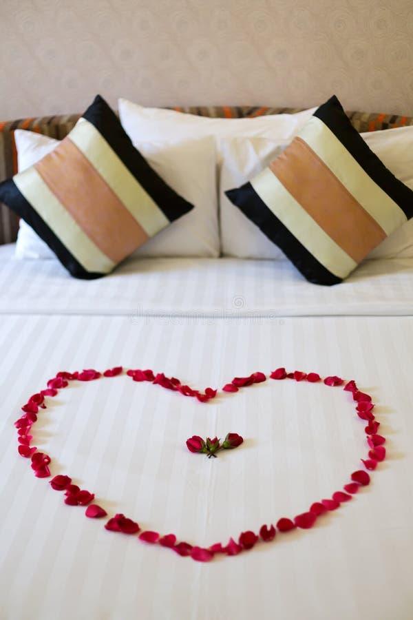 Сердце розовых лепестков клало вне на кровать стоковая фотография