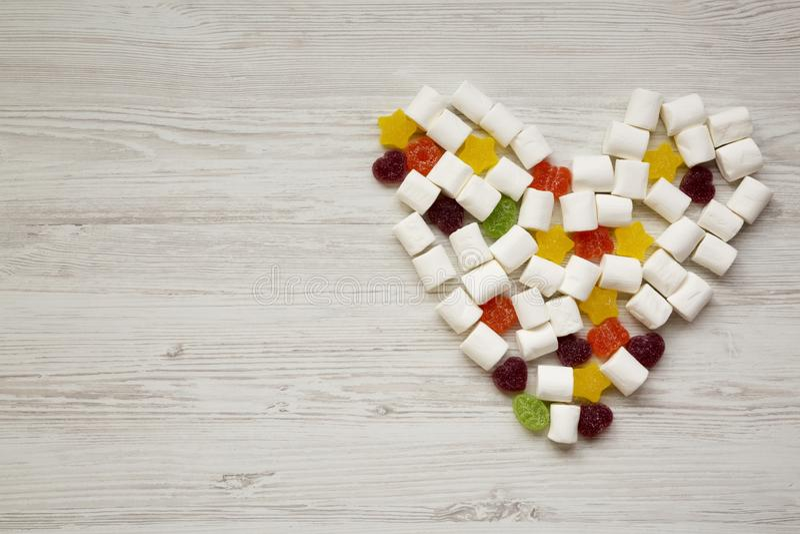 Сердце сделанное из конфет над белой деревянной предпосылкой, взгляд сверху Сверху, плоское положение, надземное скопируйте космо стоковые изображения