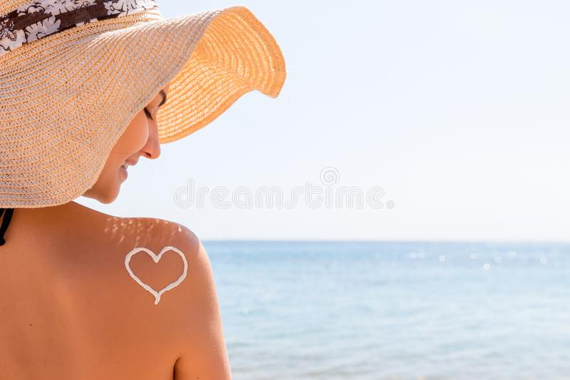 Сердце сделанное из сливк солнца нарисовано на плече женщины на пляже стоковое изображение rf