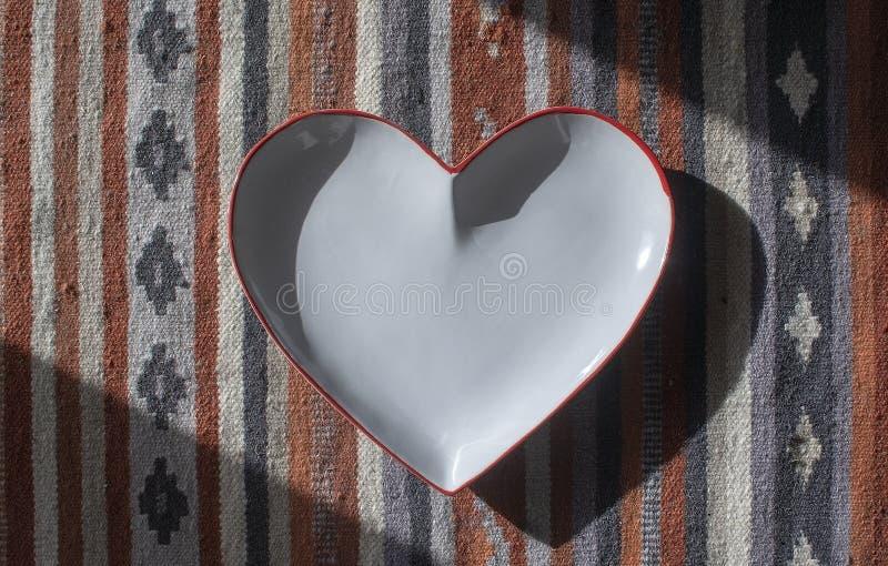Сердце сформировало белую плиту с красным краем на деревенском половике стоковые фото