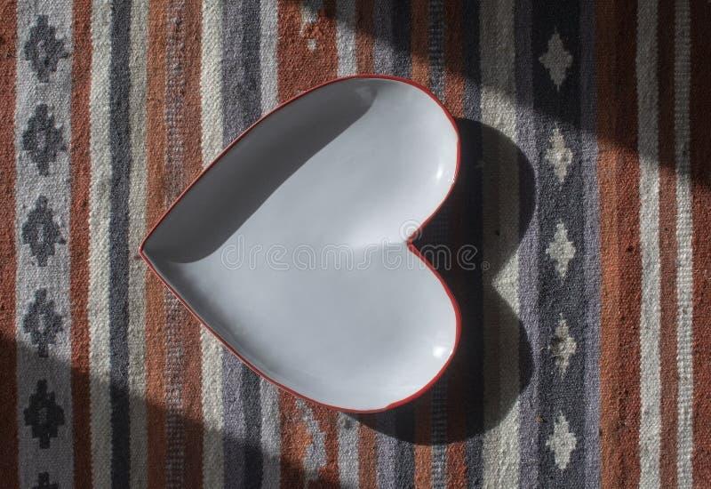 Сердце сформировало белую плиту с красным краем на деревенском половике стоковые фотографии rf