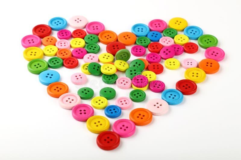 Сердце сформировало красочных шить кнопок на белизне стоковое изображение rf