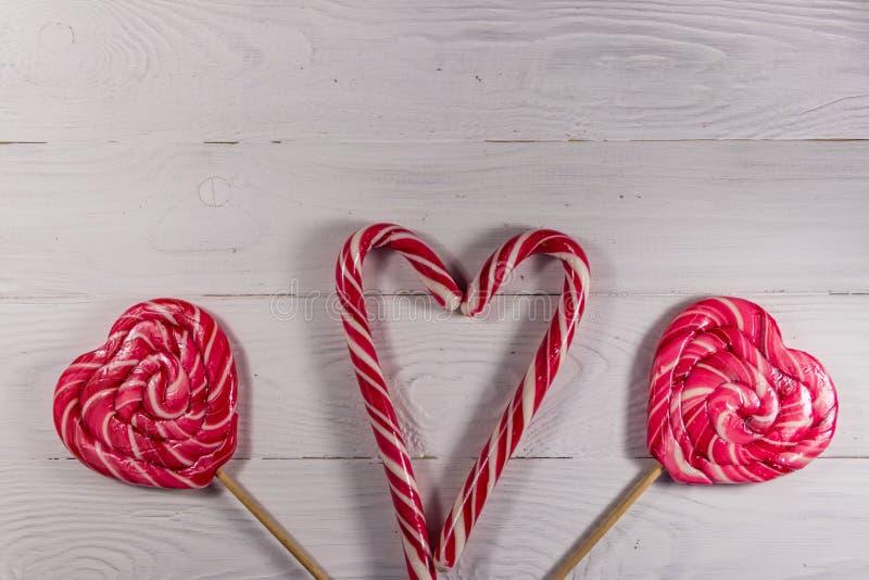 Сердце сформировало леденцы на палочке и тросточки конфеты на белой деревянной предпосылке стоковое изображение rf