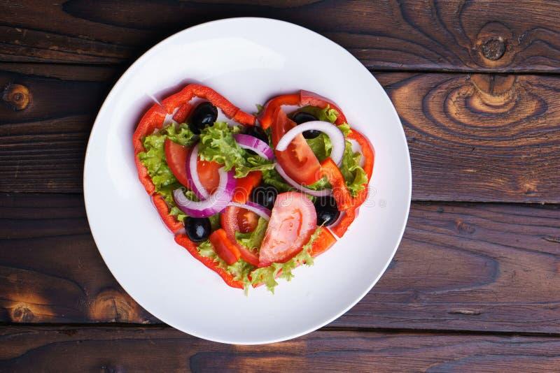 Сердце сформировало салат сырцовых овощей на плите стоковое изображение rf
