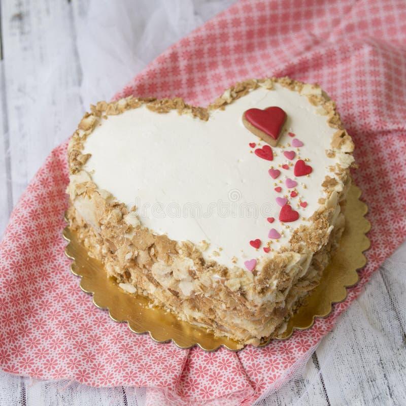 Сердце сформировало торт napoleon украшенный с печеньями в форме красных сердец на белом деревянном столе Торт дня ` s валентинки стоковая фотография
