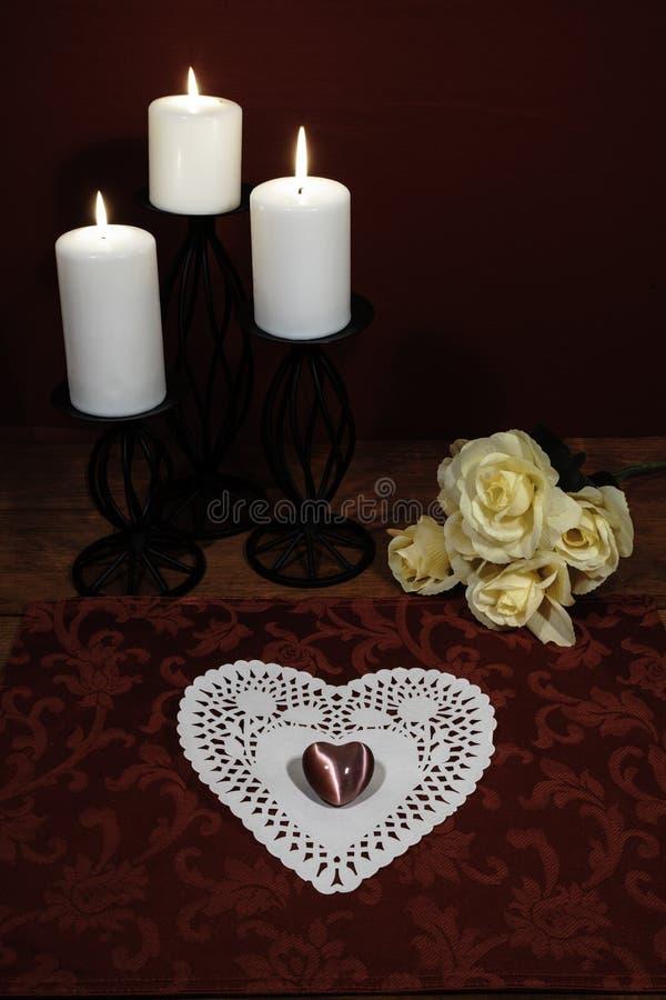 Сердце сформировало dollie и драгоценную камень, 3 белых свечи в держателях металла и букет желтых роз на деревянном столе стоковое изображение rf