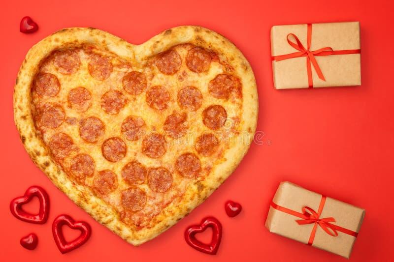 Сердце сформировало pepperoni пиццы на день Святого Валентина с подарочной коробкой на красной бумажной предпосылке стоковое фото rf