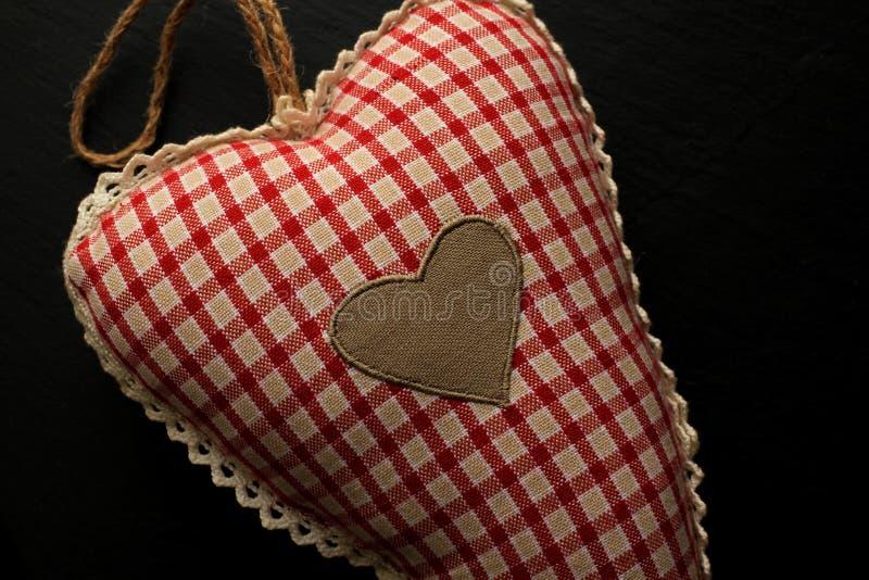 Сердце хлопка с красной и белой картиной на черной предпосылке стоковые фото