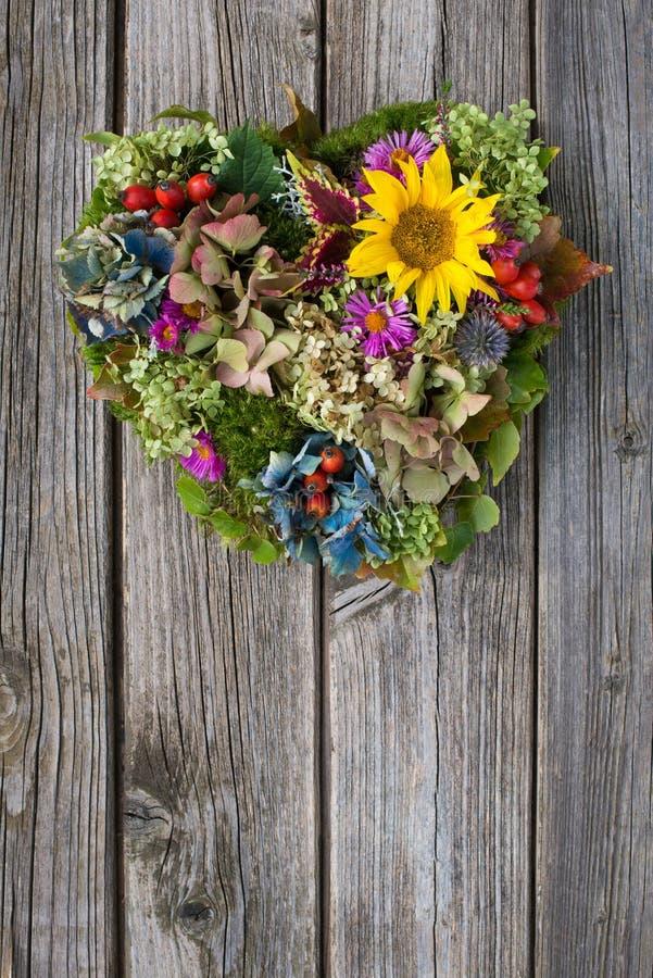 Сердце цветка осени на деревянной предпосылке стоковые изображения rf