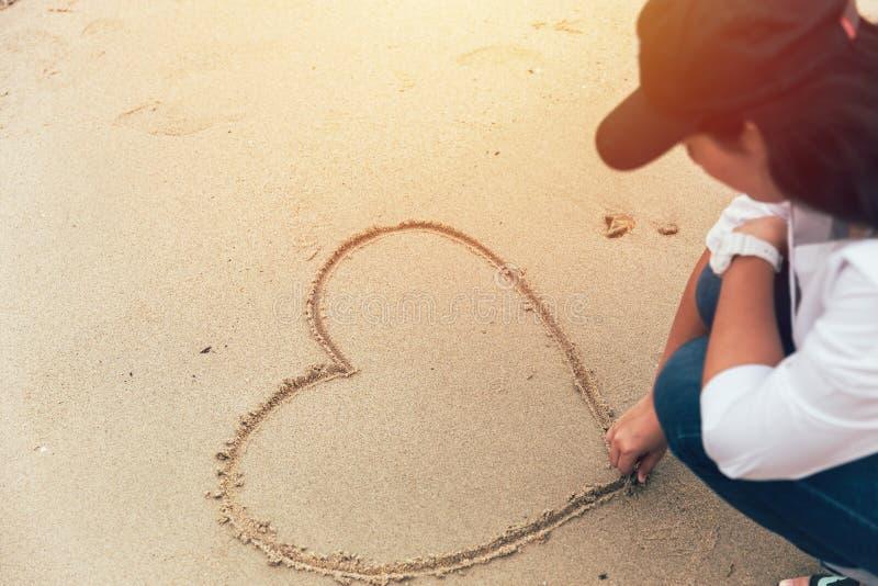 Сердце чертежа руки девушки Inlove на песке стоковые изображения