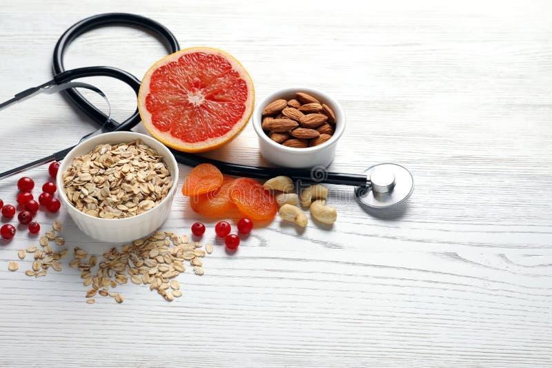 Сердц-здоровые продукты и стетоскоп на деревянной предпосылке стоковое изображение rf