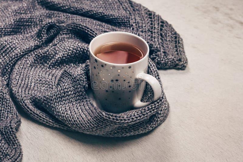 Серебристая серая связанная ткань вдоль чашки чаю на milky белой предпосылке меха стоковое фото
