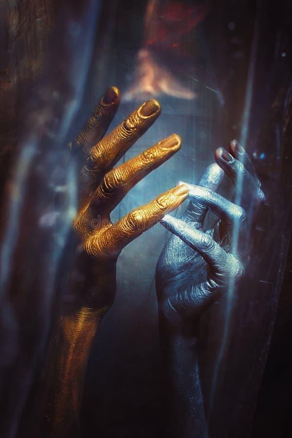 Серебристые руки на черной предпосылке стоковая фотография
