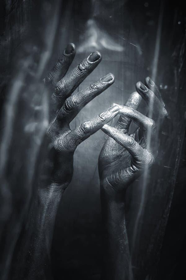 Серебристые руки на черной предпосылке стоковые фотографии rf