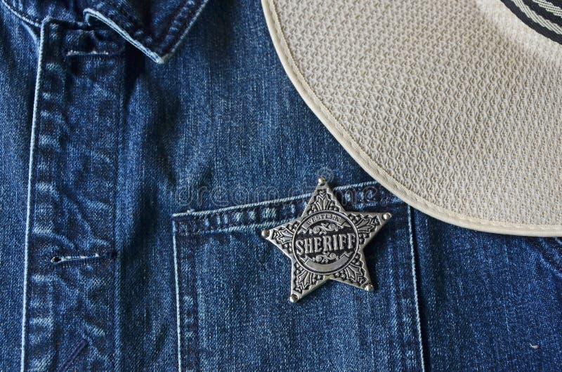 Серебряная звезда шерифа с ковбойской шляпой на голубой куртке демикотона стоковое фото
