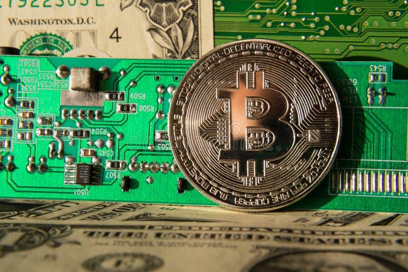 Серебряная монетка bitcoin с долларами и материнской платой компьютера, минированием cryptocurrency и инвестировать стоковое изображение rf