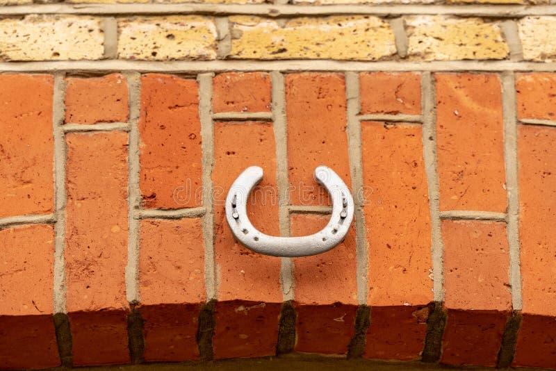 Серебряная подкова повешенная над дверью для удачи, схематическим крупным планом изображения стоковая фотография