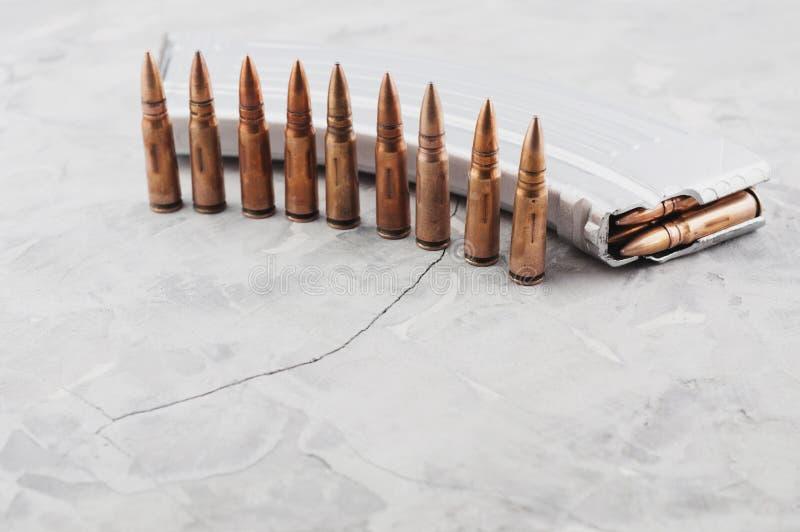 Серебряная полная кассета для штурмовой винтовки и строки пуль на сером сломанном бетоне стоковое изображение