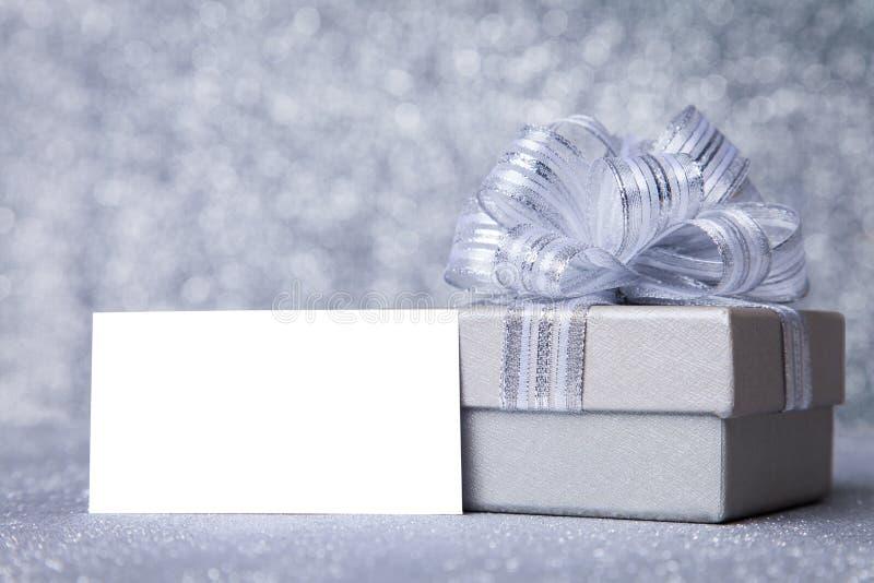 Серебряная подарочная коробка с поздравительной открыткой стоковые изображения