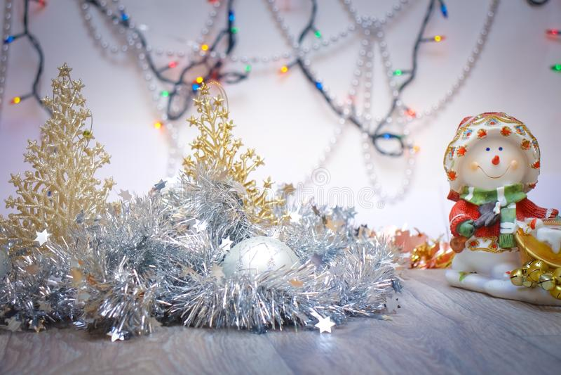 Серебряная праздничная гирлянда с орнаментами и снеговиком на предпосылке горящего Agni стоковое фото rf