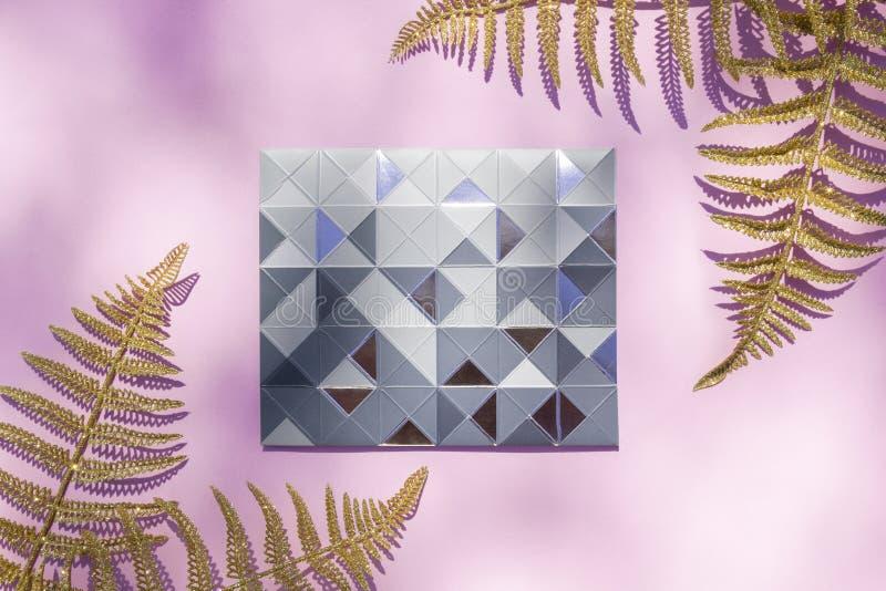Серебряная рамка сделанная треугольников и косоугольников и тропических листьев папоротника золота на розовой предпосылке солнечн стоковое фото